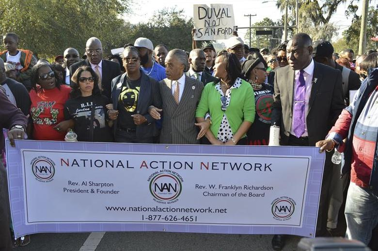 The Rev. Al Sharpton (C) links arms with Sybrina Fulton (L, dark glasses), the mother of slain teen-ager Trayvon Martin, and Phyllis Giles, whose son is in prison for what supporters call the self-defense wounding of an attacker, during a march on the Florida Capitol in Tallahassee, Florida March 10, 2014. REUTERS/Bill Cotterell