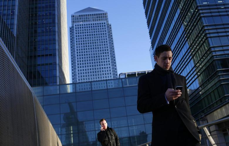 A worker looks at his phone at the Canary Wharf business district in London February 26, 2014. REUTERS/Eddie Keogh