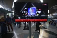 "An information screen displays a message ""Let Us Pray For Flight MH370"", regarding the missing Malaysia Airlines flight, at Kuala Lumpur International Airport in Sepang March 8, 2014. REUTERS/Samsul Said"