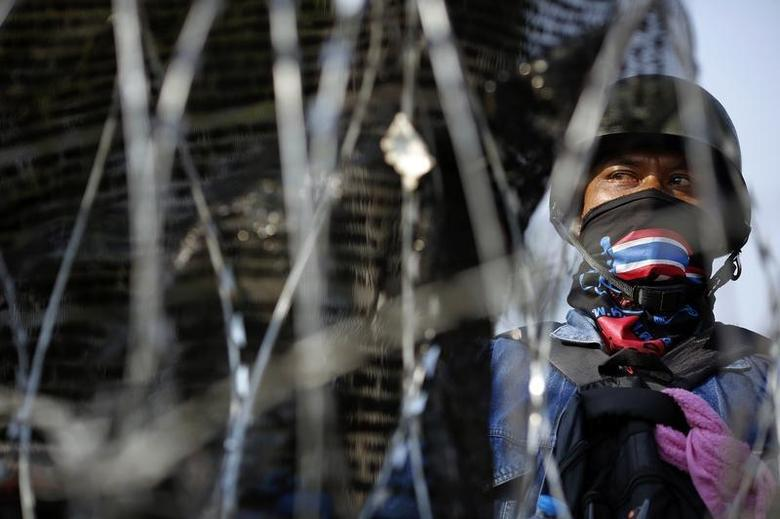 A masked anti-government protester looks out from behind a barricade near the Interior Ministry building which is being surrounded by fellow protesters, in Bangkok February 5, 2014. REUTERS/Damir Sagolj