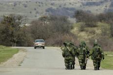 """Вооруженные люди, предположительно российские военнослужащие, идут по дороге близ военной части в селе Перевальное 10 марта 2014 года. Неизвестные вооруженные люди захватили в Крыму двух украинских журналистов, заявила в понедельник организация """"Репортеры без границ"""", предупредив, что те, кто стоит за атакой на прессу, пытаются превратить полуостров в """"информационную черную дыру"""". REUTERS/David Mdzinarishvili"""