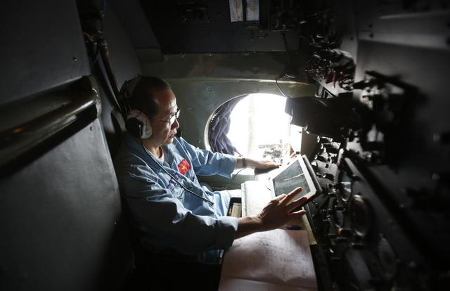 Military officer Duong Van Lanh works within a Vietnamese airforce AN-26 during a mission to find the missing Malaysia Airlines flight MH370 off Tho Chu islands March 11, 2014. REUTERS/Kham