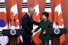 Canadian Prime Minister Stephen Harper (L) shakes hands with South Korean President Park Geun-hye during joint news conference after their meeting at the presidential Blue House in Seoul, March 11, 2014. REUTERS/Lee Jin-man/Pool