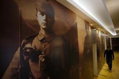 A worker walks near World War I portraits at the Franz Ferdinand hostel in Sarajevo, January 29, 2014. REUTERS/Dado Ruvic