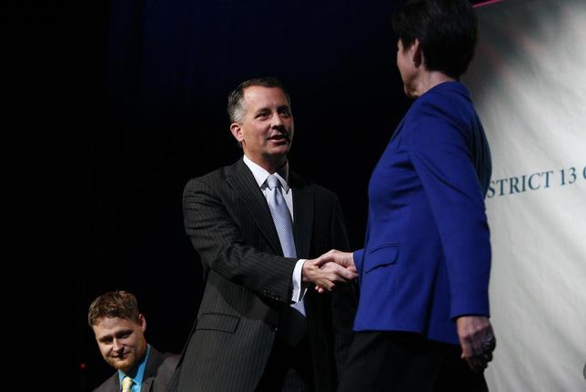 Democrat Alex Sink (C) and Republican David Jolly, both candidates for Florida's congressional District 13, shake hands before participating in a candidate forum which included Libertarian Lucas Overby (L) in Clearwater, Florida, February 25, 2014. REUTERS/Brian Blanco