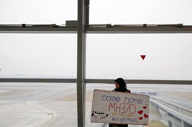 A woman holds a sign of support and hope for the passengers of the missing Malaysia Airlines flight MH370 she made and brought to the Kuala Lumpur International Airport March 11, 2014. REUTERS/Damir Sagolj