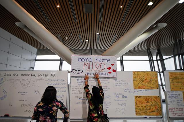 A woman places a sign of support and hope for the passengers of the missing Malaysia Airlines flight MH370 that she made and brought to the Kuala Lumpur International Airport March 11, 2014. REUTERS/Damir Sagolj