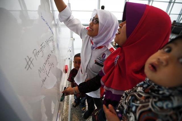 Women leave messages of support and hope for the passengers of the missing Malaysia Airlines flight MH370 at the Kuala Lumpur International Airport March 11, 2014. REUTERS/Damir Sagolj