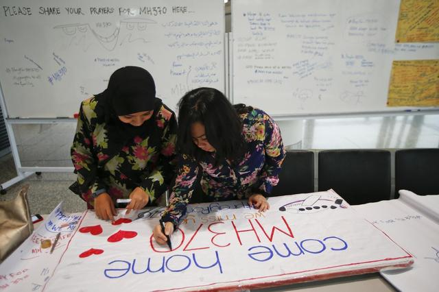 Women put the final touches to a sign of support and hope for the passengers of the missing Malaysia Airlines flight MH370 they made and brought to the Kuala Lumpur International Airport March 11, 2014. REUTERS/Damir Sagolj