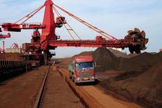 Um caminhão passa ao lado de pilhas de minério de ferro em um porto em Rizhao, na província de Shandong. Os preços do minério de ferro com entrega imediata na China estabilizaram-se nesta terça-feira, após registrarem na segunda-feira a maior queda percentual em quatro anos e meio. 03/10/2013 REUTERS/China Daily