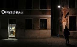 Uma pessoa passa pela frente de uma agência do UniCredit em Veneza. O UniCredit, maior banco da Itália em ativos, divulgou um surpreendente prejuízo de 14 bilhões de euros em 2013, após enormes baixas contábeis relativas a fusões e empréstimos podres, refletindo medidas para limpar o balanço antes de uma verificação da solidez do setor por reguladores europeus. 13/10/2013 REUTERS/Stefano Rellandini