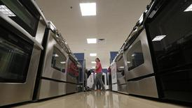 A woman walks by stoves in the appliance section at a Sears store in Schaumburg, Illinois near Chicago in this file photo taken September 23, 2013. REUTERS/Jim Young/Files