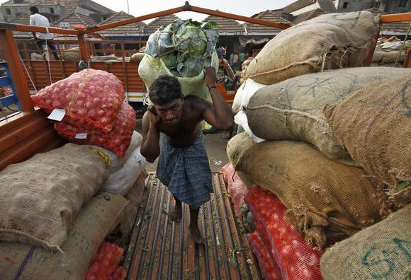 A labourer carries a sack filled with cabbage to load it onto a supply van at a vegetable wholesale market in Chennai February 14, 2014. REUTERS/Babu