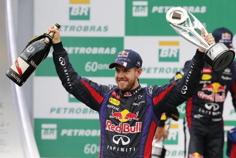 Red Bull Formula One driver Sebastian Vettel of Germany celebrates with the trophy on the podium after the Brazilian F1 Grand Prix at the Interlagos circuit in Sao Paulo November 24, 2013. REUTERS/Paulo Whitaker