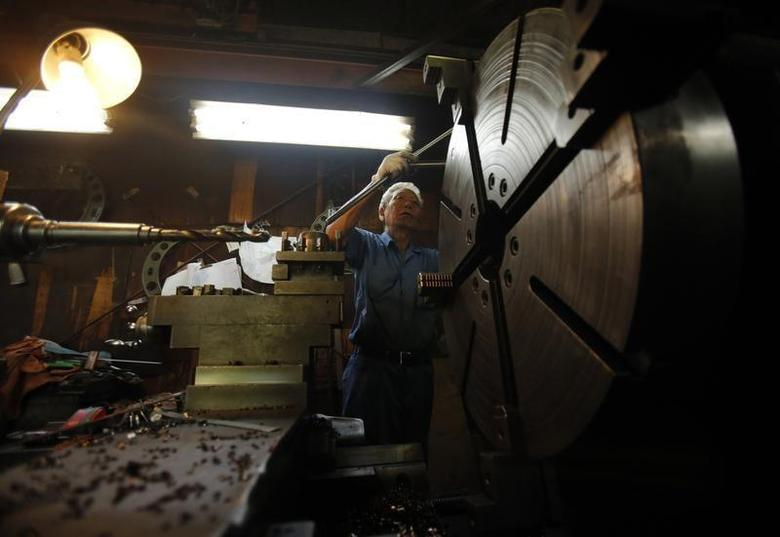 A man produces machine parts inside a factory in Tokyo August 12, 2013. REUTERS/Yuya Shino