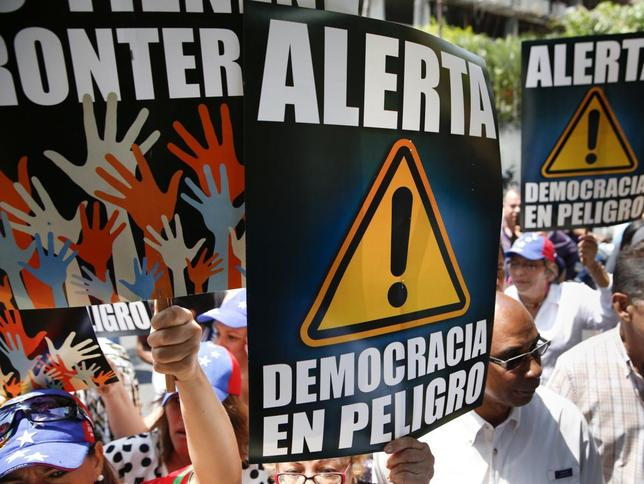 Anti-government protesters hold placards during a gathering against Nicolas Maduro's government outside the Embassy of Portugal in Caracas March 11, 2014. REUTERS/Carlos Garcia Rawlins