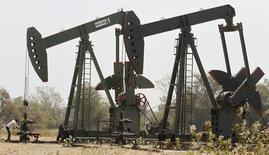 Нефтяные станки-качалки на месторождении компании ONGC в индийском городе Ахмадабад 1 марта 2012 года. Цены на нефть снижаются, так как опасения за спрос в двух крупнейших потребителях сильнее страха перед возможными перебоями в снабжении из-за ситуации на Украине. REUTERS/Amit Dave