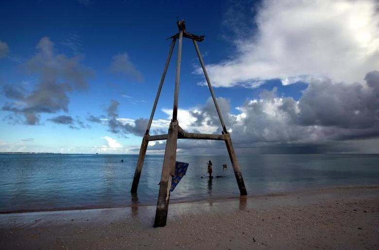 Binata Pinata stands on top of a rock underneath an old tower as she waits for her husband Kaibakia to hand her the fish he is catching, on Bikeman islet, located off South Tarawa in the central Pacific island nation of Kiribati May 25, 2013. REUTERS/David Gray
