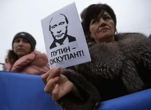 A woman holds a sign with a portrait of Russian President Vladimir Putin and the words ''Putin - Occupant'' during a pro-Ukrainian rally in Simferopol March 11, 2014. REUTERS/David Mdzinarishvili