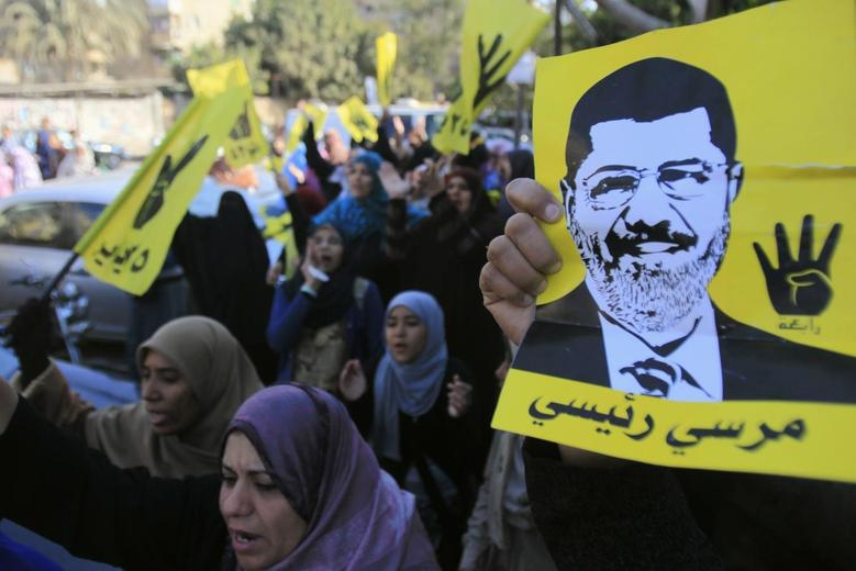 Supporters of the Muslim Brotherhood and ousted Egyptian President Mohamed Mursi shout slogans against the military and interior ministry while holding his poster and gesturing with four fingers in front of Al Rayyan mosque after Friday prayers in the southern suburb of Maadi, on the outskirts of Cairo December 27, 2013 FILE PHOTO. REUTERS/Amr Abdallah Dalsh