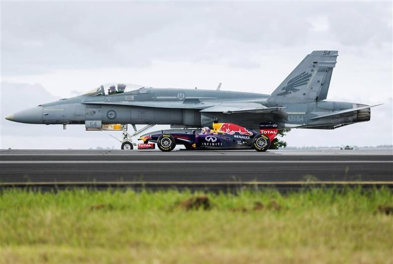 Formula One driver Daniel Ricciardo of Australia drives his Infiniti Red Bull car alongside a Royal Australian Air Force F/A-18 Hornet plane during a promotional event at a regional Air Force base near Melbourne, in this March 12, 2014 handout photo provided by Red Bull. The Australian Formula One Grand Prix will be held on March 16. REUTERS/Andy Green/Red Bull/Handout via Reuters