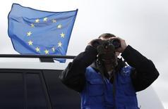 Наблюдатель миссии ЕС в деревне Двани смотрит в бинокль, как российские солдаты возводят изгородь вдоль фактической границей между Грузией и отколовшейся от неё автономией Южная Осетия 4 октября 2013 года. Государства Евросоюза согласовали проект санкций против России, предполагающие, в том числе, визовые ограничения и замораживание активов тех, кто отвечает за нарушение суверенитета Украины, свидетельствует документ, с которым ознакомился Рейтер. REUTERS/David Mdzinarishvili