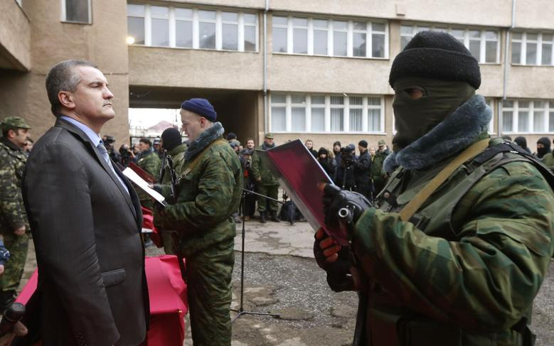 Sergei Aksyonov, Crimea's pro-Russian prime minister, stands as a member of a pro-Russian self defence unit takes an oath to Crimea government in Simferopol March 10, 2014. REUTERS/Vasily Fedosenko