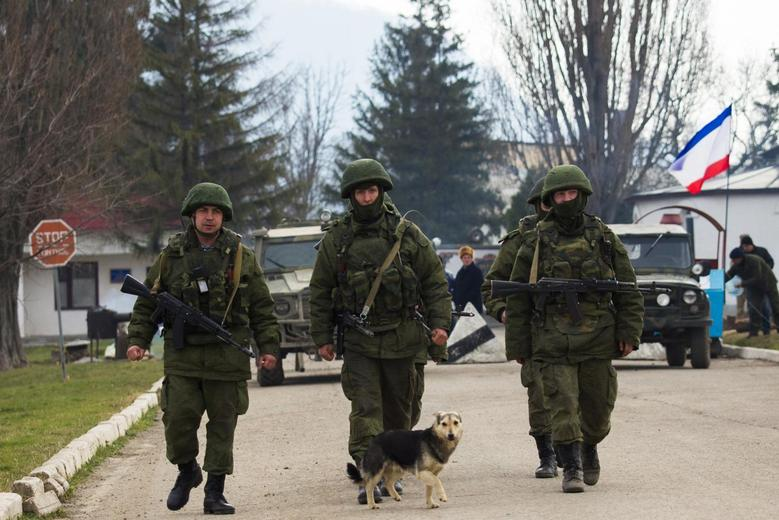 Armed men, believed to be Russian servicemen, march outside an Ukrainian military base in the village of Perevalnoye near the Crimean city of Simferopol, March 12, 2014. REUTERS/Thomas Peter