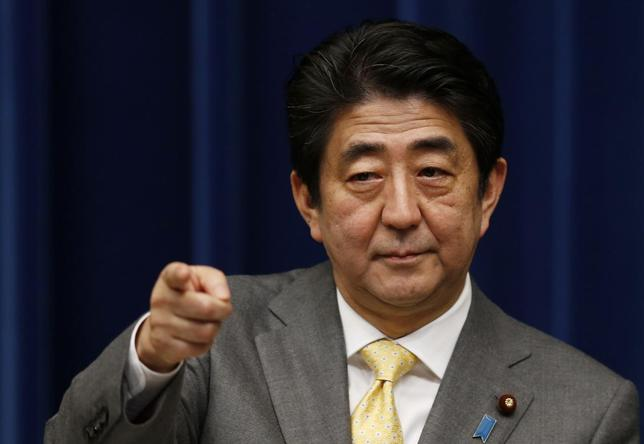 Japan's Prime Minister Shinzo Abe points to a reporter during a news conference at his official residence in Tokyo March 10, 2014, a day before the third anniversary of the March 11, 2011 earthquake, tsunami and nuclear crisis that struck the nation's northeast. REUTERS/Issei Kato