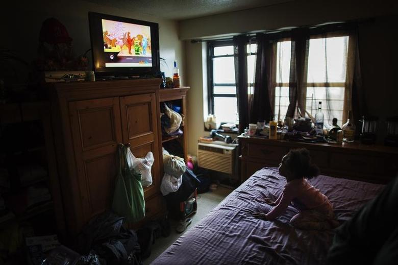 A young child watches television in an NYCHA apartment after receiving electricity just minutes before for the first time following Hurricane Sandy in the Brooklyn borough neighborhood of Coney Island in New York November 13, 2012. REUTERS/Lucas Jackson