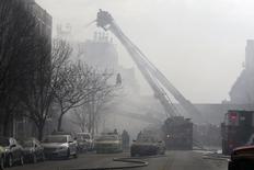 Пожарные тушат рухнувшие здания на Манхэттене, 12 марта 2014 года. Две женщины погибли и не менее 18 человек получили ранения в результате обрушения двух зданий в Верхнем Манхэттене в Нью-Йорке, однако число жертв может вырасти, поскольку люди могут находиться под завалами, сообщили власти. REUTERS/Mike Segar
