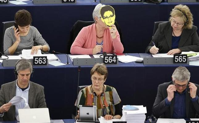 France's Nicole Kiil-Nielsen (2nd row, C), a member of the group of the Greens/European Free Alliance of the European Parliament, holds up a portrait of former U.S. spy agency National Security Agency (NSA) contractor Edward Snowden, during a voting session on the U.S. NSA's surveillance programme and its impact on the fundamental rights of European Union (EU) citizens, at the European Parliament in Strasbourg, March 12, 2014. REUTERS/Vincent Kessler