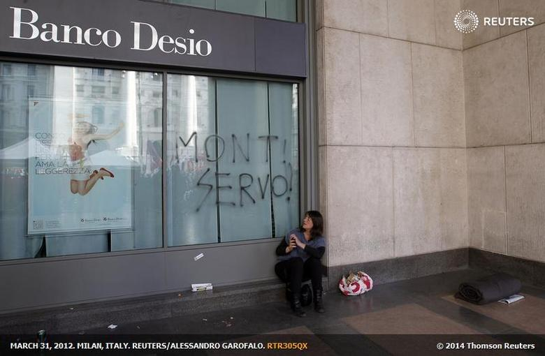 A woman looks at graffiti on Banco Desio bank's window in front of Milan's stock exchange during a demonstration against government in Milan, March 31, 2012. REUTERS/Alessandro Garofalo
