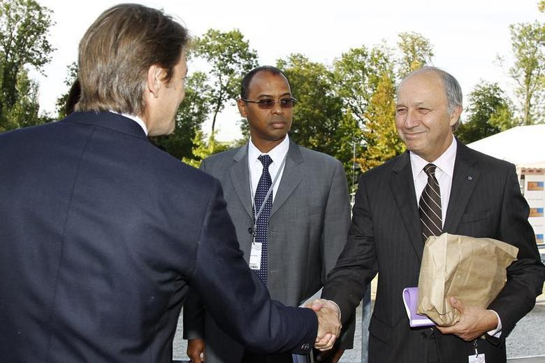 French Finance Minister Francois Baroin (L) shakes hands with socialist party member Laurent Fabius (R) as Ivory Coast's Thierry Tanoh (C), IFC's (International Finance Corporation) Vice President for Sub-Saharan Africa, Latin America and the Caribbean and Western Europe, looks on at the French employers' body MEDEF union summer forum on the campus of the HEC School of Management in Jouy-en-Josas, near Paris, August 31, 2011. REUTERS/Charles Platiau