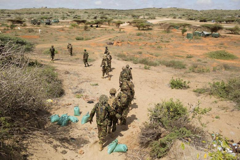 Kenya Defence Forces (KDF) soldiers, who are part of the African Mission in Somalia (AMISOM), march to their armoured vehicles before an area patrol on the outskirts of the controlled area of the old airport in the coastal town of Kismayu in southern Somalia November 12, 2013. REUTERS/Siegfried Modola