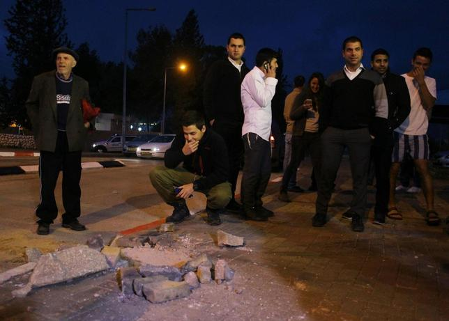 Israeli onlookers survey the damage caused by a rocket which was fired from the Gaza Strip and landed in the southern Israeli town of Sderot March 12, 2014. REUTERS/Ilan Assayag