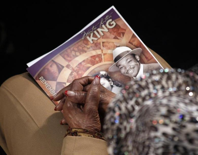 A visitor holds a commemorative booklet as she listens during the Martin Luther King, Jr. 46th Annual Commemorative Service at Ebenezer Baptist Church in Atlanta, Georgia January 20, 2014. REUTERS/Tami Chappell