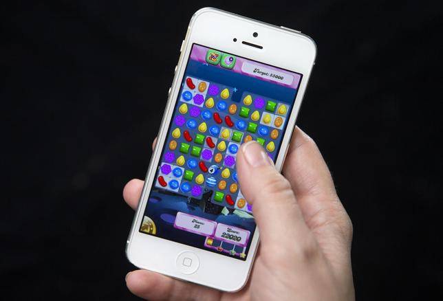 A woman poses for a photo illustration with an iPhone as she plays Candy Crush in New York February 18, 2014. REUTERS/Carlo Allegri