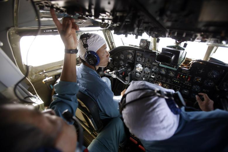 Military officers work in the cockpit of a Vietnam Air Force AN-26 aircraft during a mission to find the missing Malaysia Airlines flight MH370, that disappeared from radar screens in the early hours of Saturday, off Con Dao island March 12, 2014. REUTERS/Kham