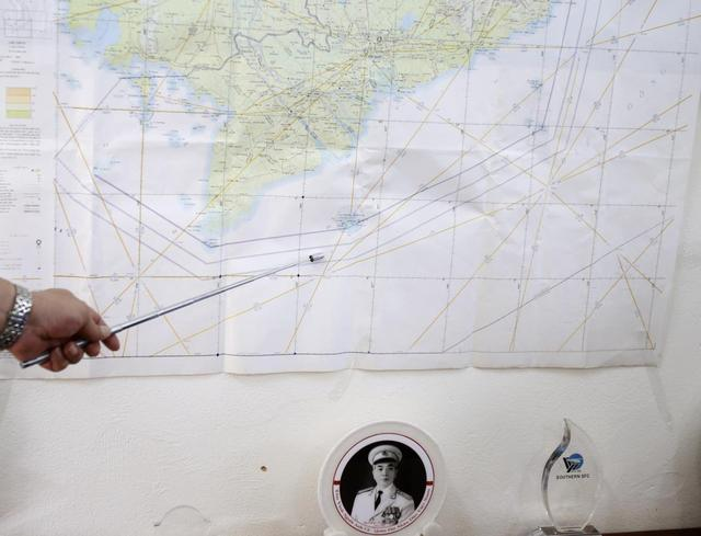 Air Force Deputy Chief of Staff Senior Colonel Do Duc Minh points to the map of a search area to find the missing Malaysia Airlines flight MH370, during a news briefing at a military airport in Ho Chi Minh city March 13, 2014. REUTERS/Kham