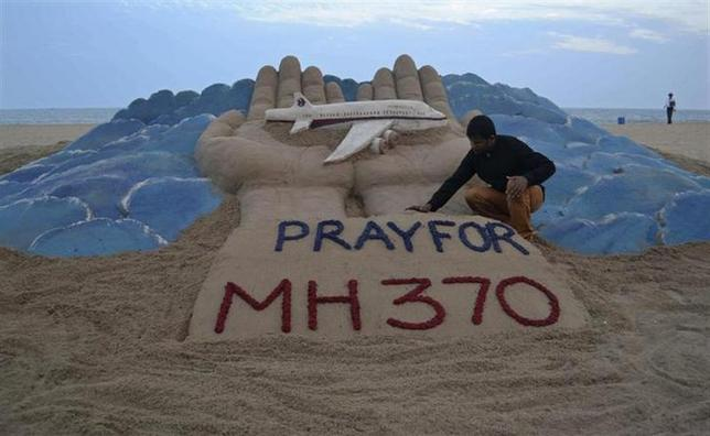 Indian sand artist Sudarshan Pattnaik works on a sand sculpture of missing Malaysian Airlines flight MH370, at golden beach at Puri in the eastern Indian state of Odisha March 12, 2014. REUTERS/Stringer