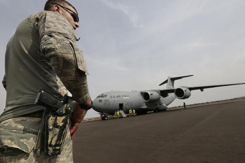 An American soldier stands guard after the arrival of a U.S. Air Force C-17 transport plane with French troops at the airport in Bamako January 22, 2013. REUTERS/Eric Gaillard