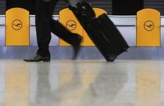 Человек проходит мимо символов Lufthansa в аэропорту Франкфурте-на-Майна 11 февраля 2014 года. Крупнейшая авиакомпания Германии Lufthansa уверена в успешном завершении программы реструктуризации после хорошего квартального отчета. REUTERS/Ralph Orlowski