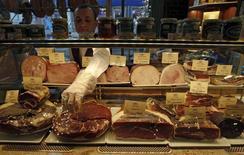 Человек продает мясо на рынке в Санкт-Петербурге 8 февраля 2013 года. Один из крупнейших в РФ производителей мяса Мираторг снизил чистую прибыль в 2013 году на 14,1 процента до 9,6 миллиарда рублей на фоне падения цен на свинину после присоединения России к ВТО и роста цен на зерно, сообщила компания в четверг. REUTERS/Alexander Demianchuk