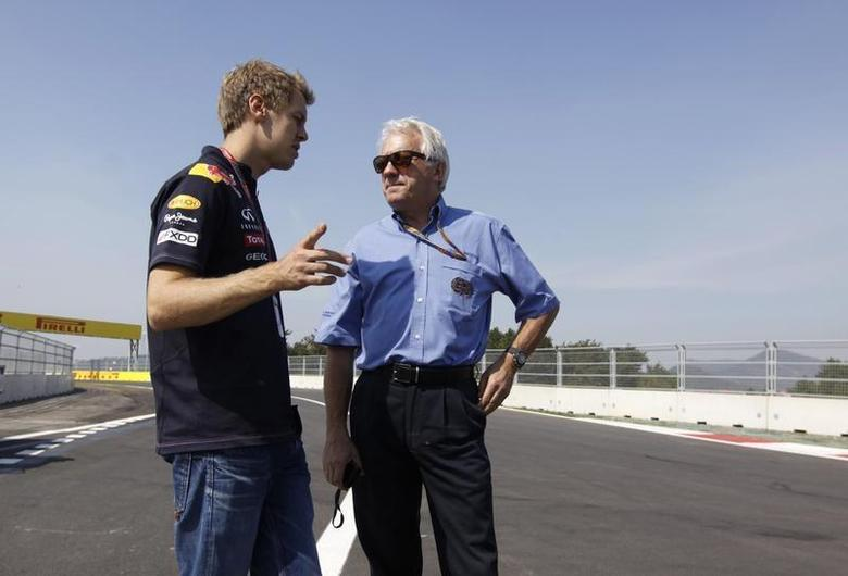 Red Bull Formula One driver Sebastian Vettel (L) of Germany speaks to FIA race director Charlie Whiting as they walk the circuit ahead of the South Korean F1 Grand Prix at the Korea International Circuit in Yeongam October 13, 2011. REUTERS/Lee Jae-Won