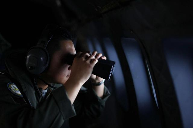 A crew member from the Royal Malaysian Air Force uses binoculars onboard a Malaysian Air Force CN235 aircraft during a Search and Rescue (SAR) operation to find the missing Malaysia Airlines flight MH370, in the Straits of Malacca March 13, 2014. REUTERS/Samsul Said