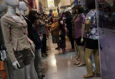 Uma mulher procura roupas em uma loja no Brás, em São Paulo. As vendas no comércio varejista brasileiro avançaram 0,4 por cento em janeiro na comparação com o mês anterior, resultado melhor do que o esperado e suficiente para reverter a contração vista em dezembro e que havia interrompido nove meses seguidos de expansão. 09/08/2013 REUTERS/Nacho Doce