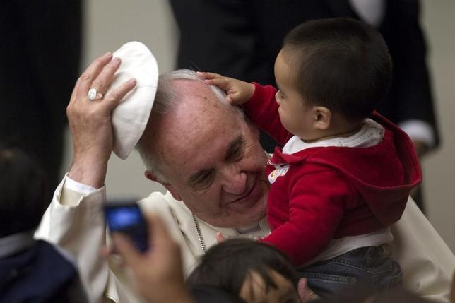 Pope Francis has his skull cap removed by a child during an audience with children assisted by volunteers of Santa Marta institute in Paul VI hall at the Vatican December 14, 2013. REUTERS/Giampiero Sposito