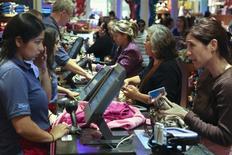 """Un grupo de clientes realizan unas compras en una tienda de Disney durante las ofertas del """"Black Friday"""" en Glendale, EEUU, nov 29 2013. Las ventas minoristas de Estados Unidos repuntaron en febrero y la cifra de nuevos pedidos de ayuda por desempleo tocó un nuevo mínimo de tres meses en la última semana, lo que sugiere cierta fortaleza de la economía después que un fuerte invierno paralizó abruptamente la actividad en meses recientes. REUTERS/Jonathan Alcorn"""