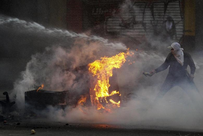 An anti-government protester tries to set fire to a barricade while up against the police's water canon during clashes in Caracas March 12, 2014. REUTERS/Christian Veron